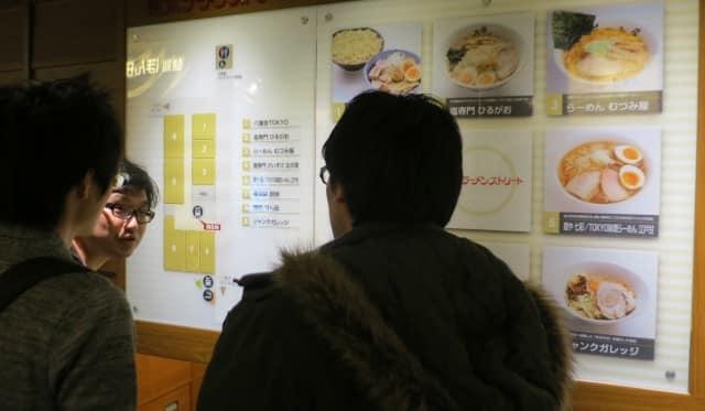 Tokyo locals argue over their ramen choices. Ramen Street Tokyo Japan