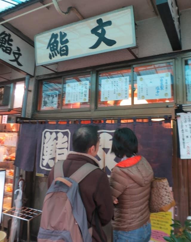 Customer line up outside Sushi Bun at Tsukiji Market in Tokyo Japan