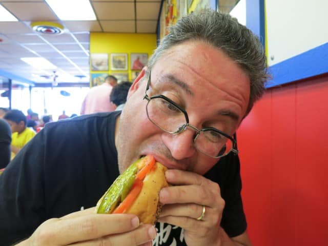 Daryl Bites into a Chi Dog at Hot Doug's in Chicago