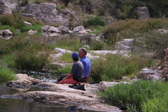 Hikers enjoy a peaceful moment aside a stream in the Parco della Murgia Materana. The park is just a short hillside walk down from the center of Matera's Sassi district. Visit Matera Italy