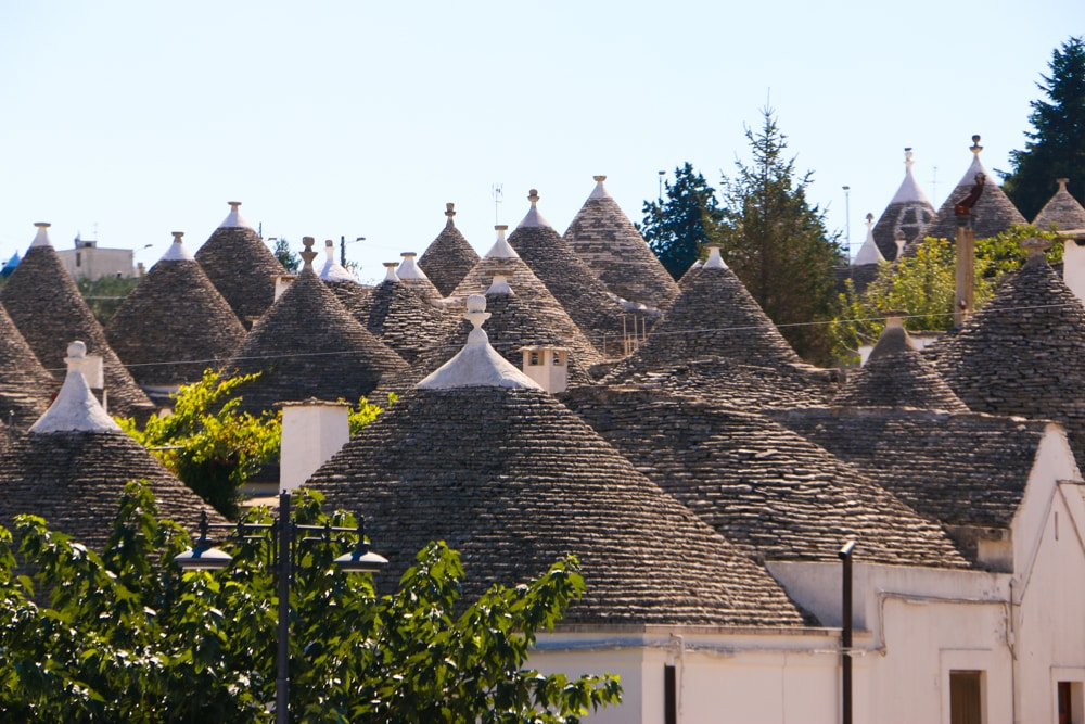 The Puglian town of Alberobello is filled with trulli, dry stone huts with conical roofs. These simple structures give the city a fairytale-like feeling. Puglia in a Day Trip to Puglia