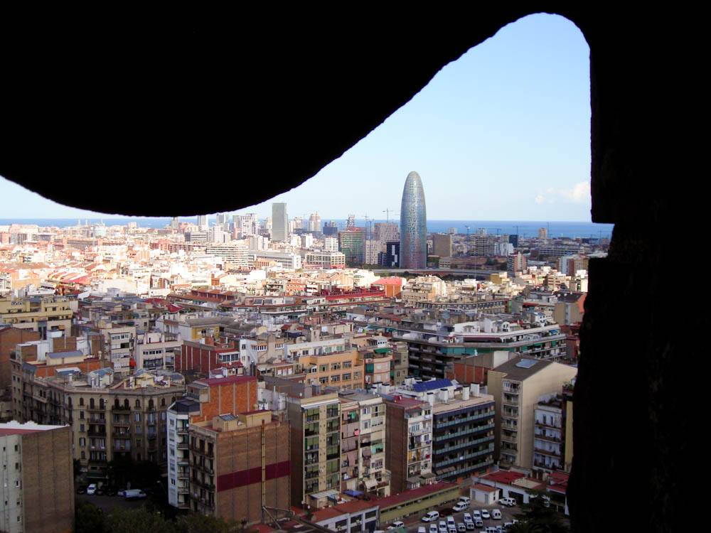 The view from Sagrada Familia shows the colorful Barcelona cityscape bordered by the blue Mediterranean Sea.
