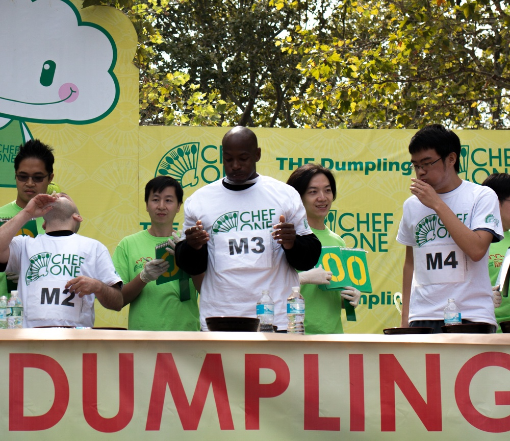 Male contestants eat to win at the dumpling eating contest. The winning man ate 78 dumplings in two minutes. NYC Dumpling Festival