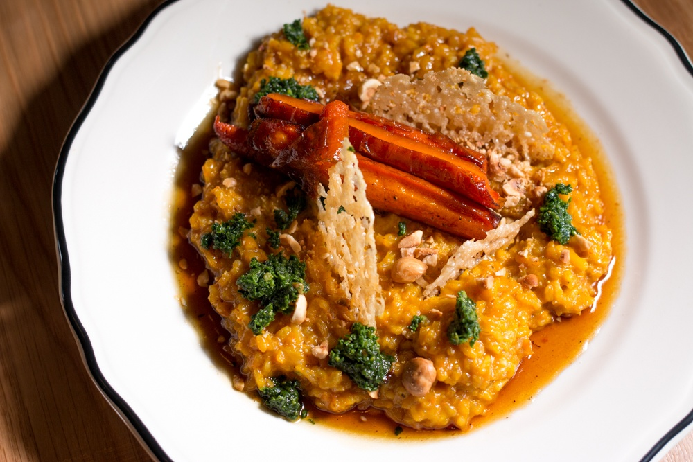 Roasted Carrot Risotto is prepared with Carolina gold rice, kale pesto, parmesan crisps and hazelnuts. The popular vegetarian dish uses carrots to excellent effect, coloring the rice with its bright orange hue.