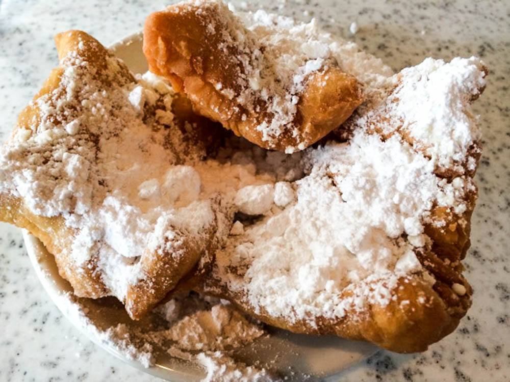 Cafe Du MondeThis massof fried dough goodness is generouslysmotheredwith powdered sugar. The only thing missing from this photo is the CaféAu Lait. Cafe Du Monde 10 Cheap Eats New Orleans 2foodtrippers