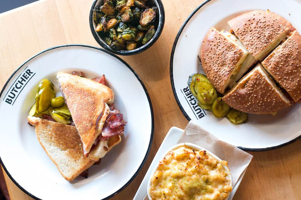 A lunch of two sandwiches and two sides is more than enough to satisfy two hungry diners at Cochon Butcher. Pictured here are the Buckboard Bacon Melt and Muffaletta sandwiches along with two sides - the Marinated Brussel Sprouts and the Mac and Cheese. 10 Cheap Eats New Orleans 2foodtrippers