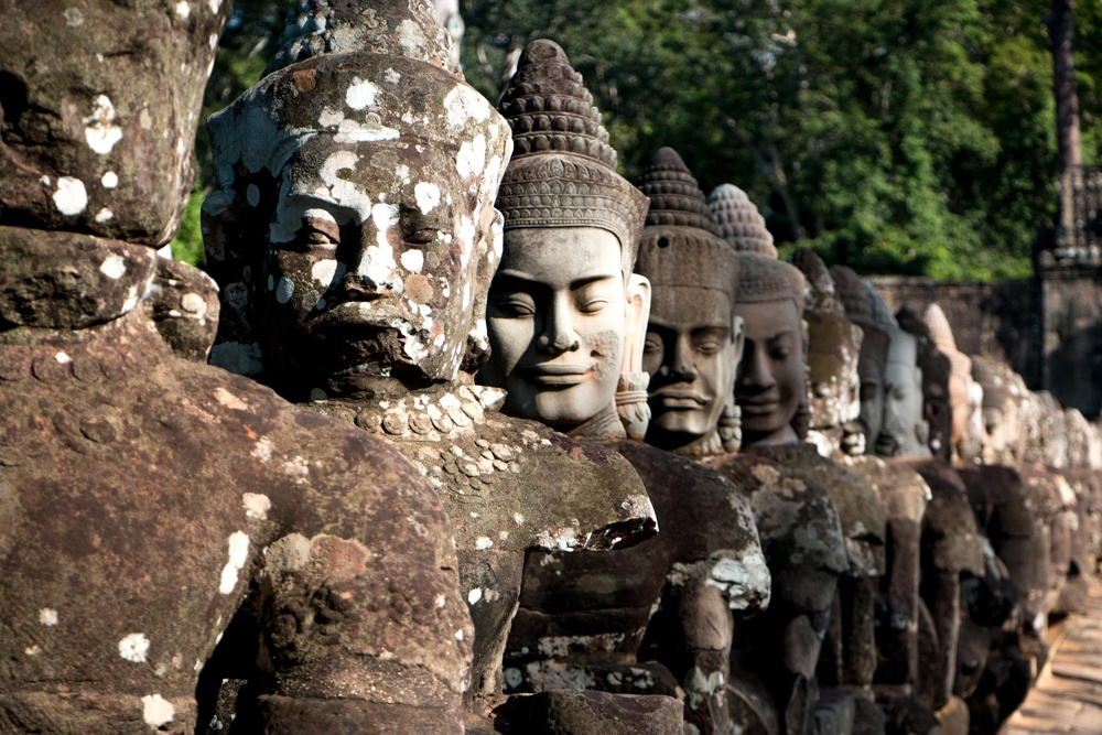 Ancient stone statues greet visitors at the South Gate entrance to the city of Angkor Thom. Cambodian Adventure in Siem Reap