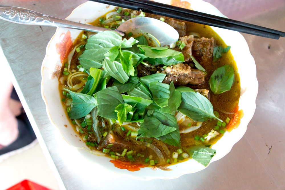 Saigon is a soup city! This bowl includes meat, noodles and a ton of fresh herbs. How To Eat in Saigon Food- A Ho Chi Minh City Food Guide