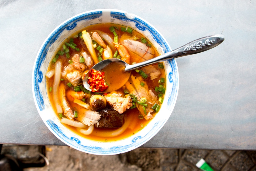 We found this bowl of Banh Canh on the sidewalk near Maison Marou. Loaded with seafood, wide noodles and mushrooms, it was well worth its cost of around $2 US. How To Eat in Saigon Food- A Ho Chi Minh City Food Guide