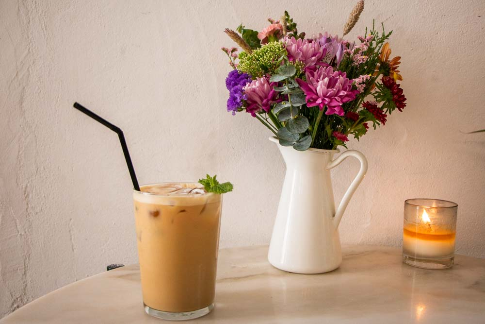 Iced Latte Next to Flowers and Candle at Dear Breakfast in Lisbon