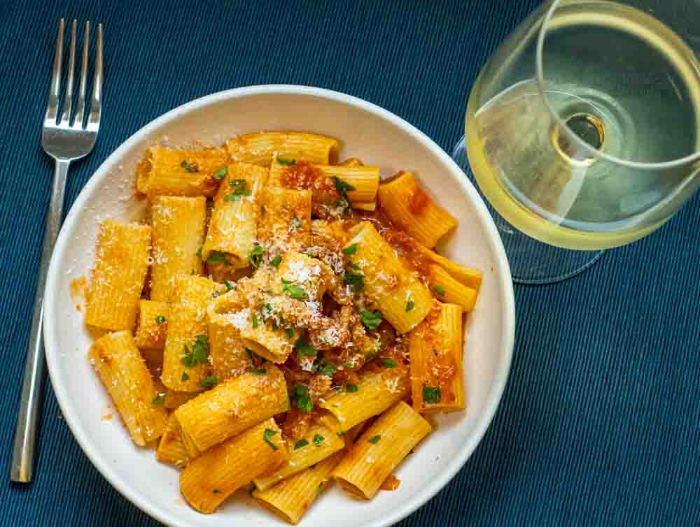 Rigatoni Amatriciana with White Whine on Blue Place Mat