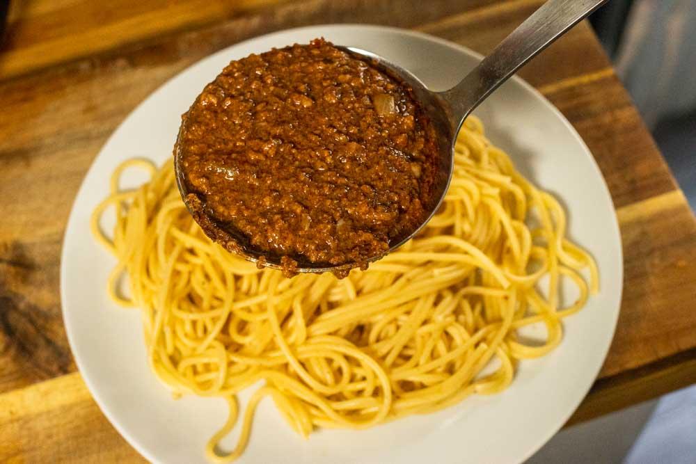 Ladeling Cincinnati Chili on Spaghetti