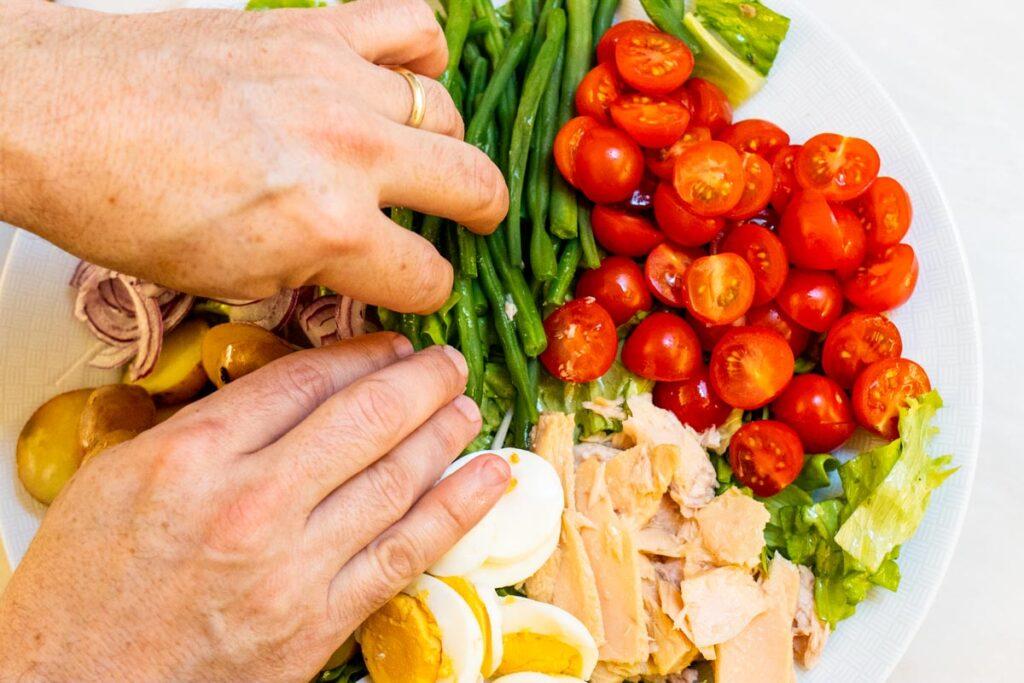 Assembling Cobb Salad on White Plate