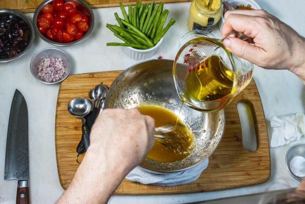 Drizzling olive oil into Red Wine Vinegar for Vinaigrette