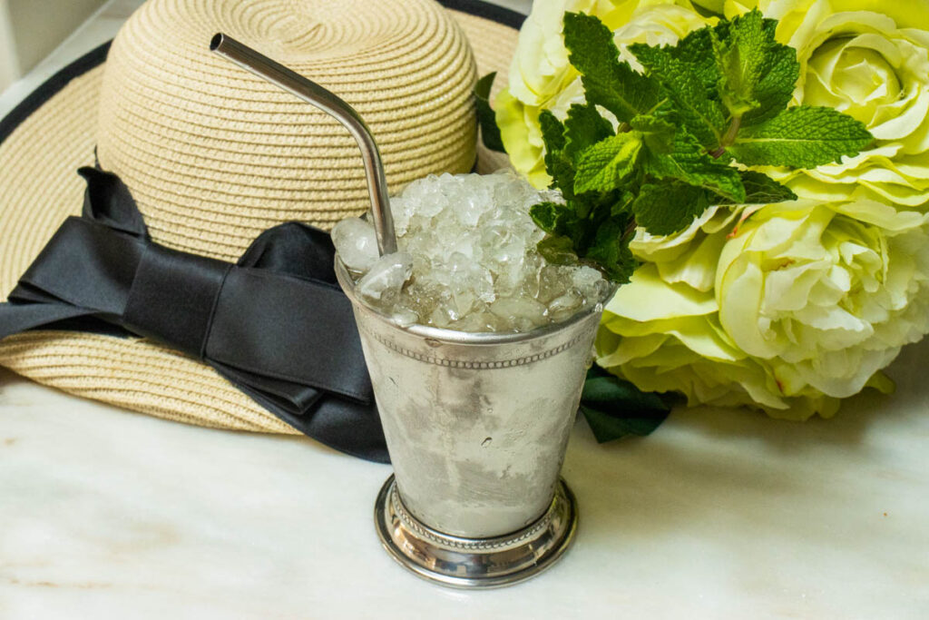 Mint Julep Next to Hat and Yellow Flowers