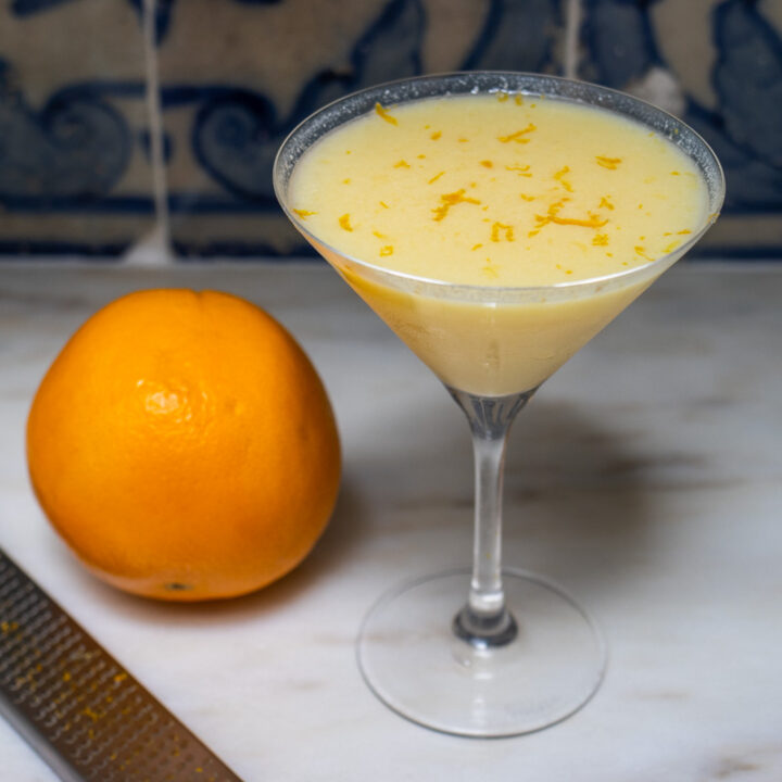 Orange Creamsicle Cocktail with Orange Next to Blue Tiles