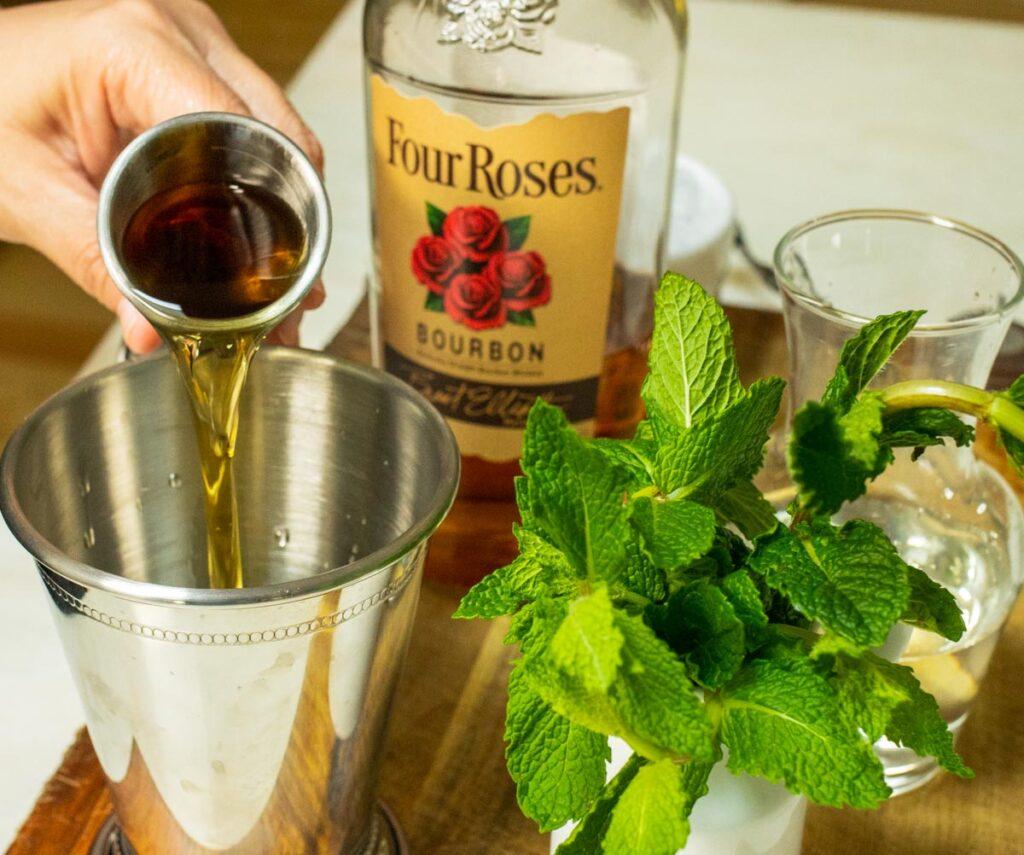 Pouring Bourbon into Mint Julep