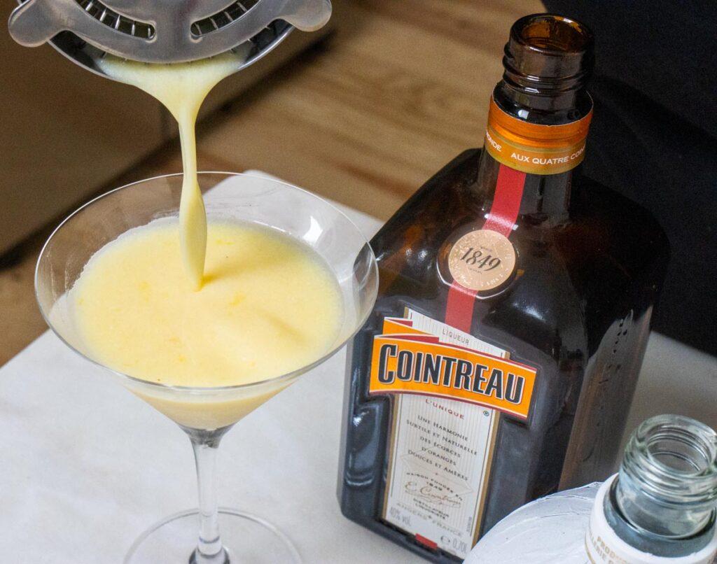 Straining Orange Creamsicle Cocktail into Glass