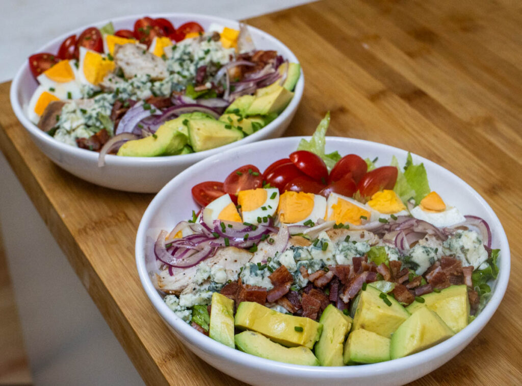 Two Bowls of Cobb Salad on Wooden Board