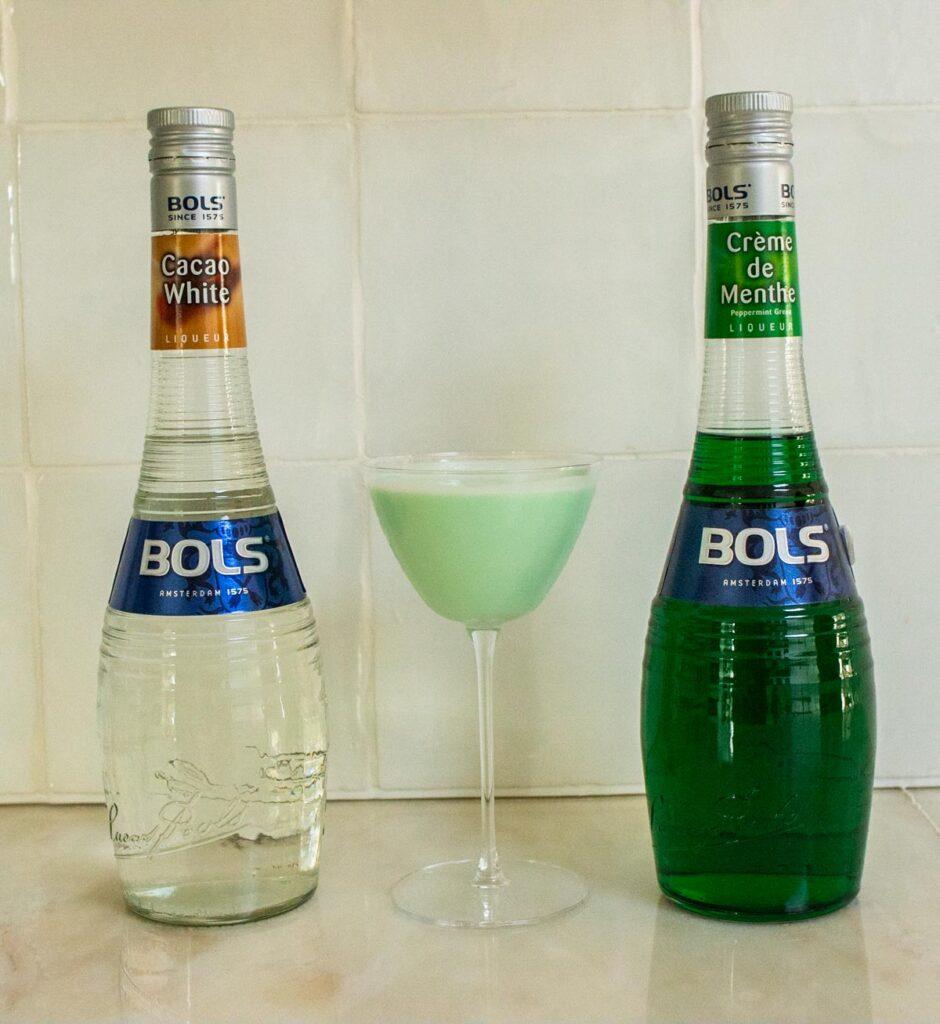 Grasshopper Cocktail Next to Liqueur Bottles