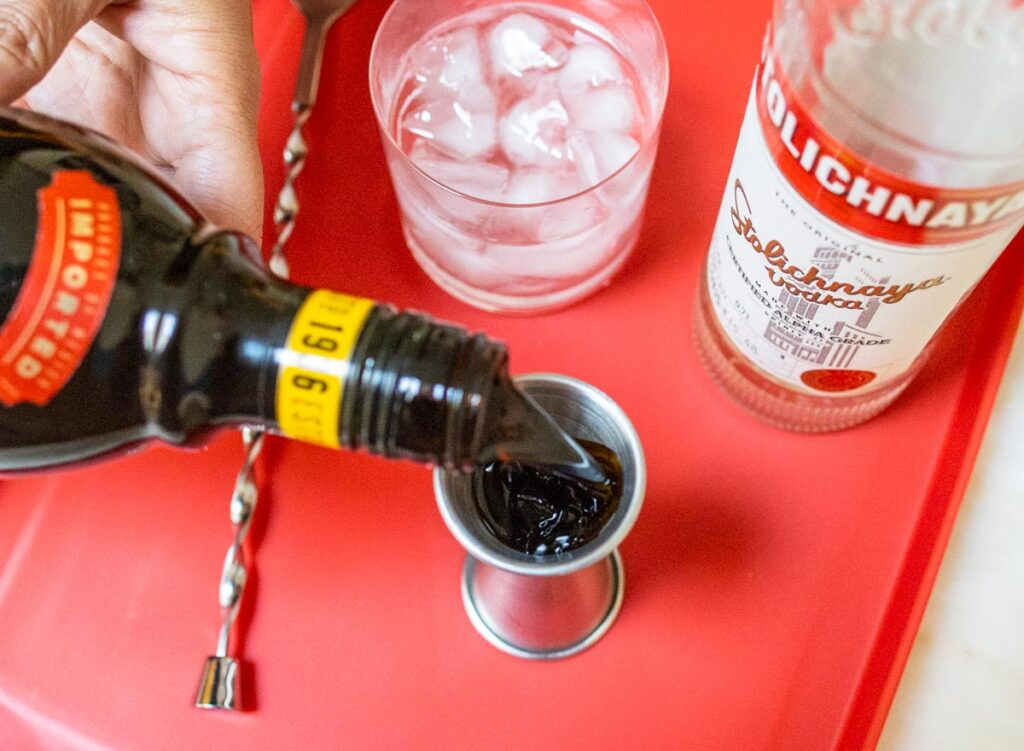 Pouring Kahlua for Black Russian Cocktail