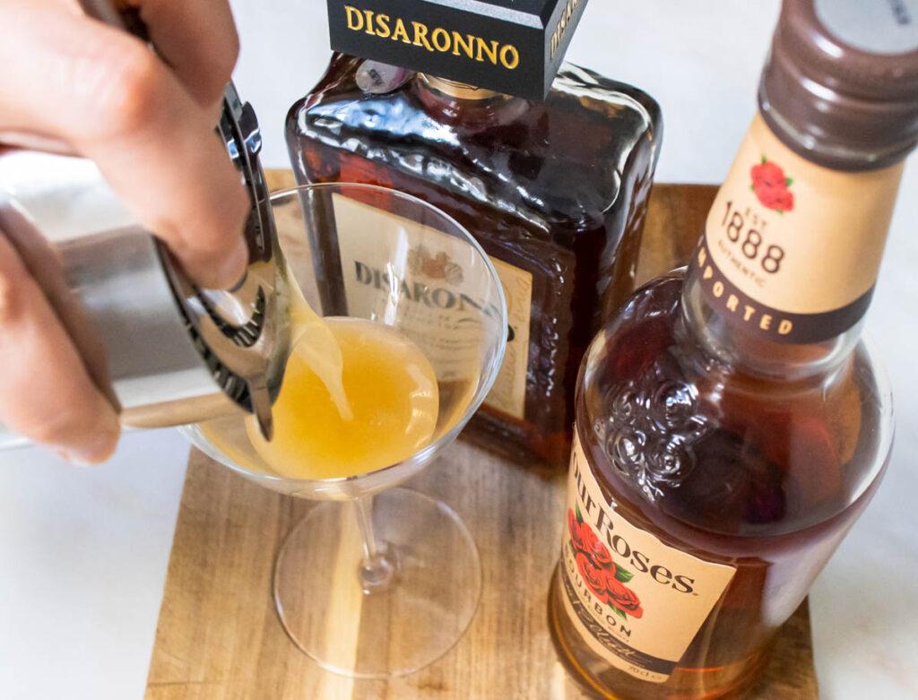 Straining an Amaretto Sour into a Glass