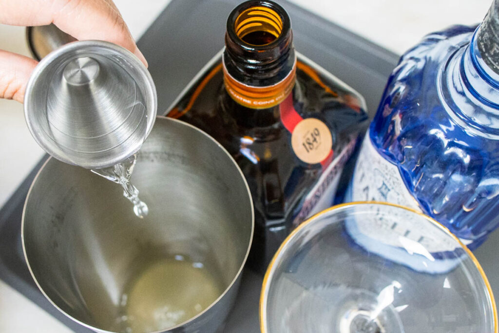 Pouring Cointreau to a White Lady Cocktail