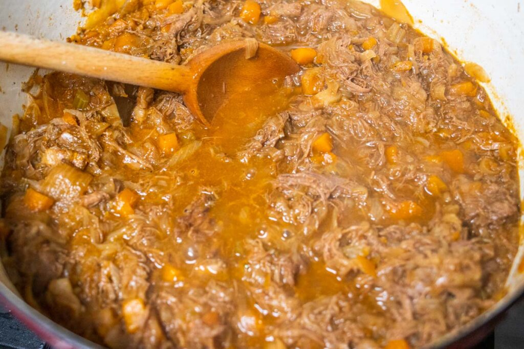 Stirring Genovese Sauce with a Wooden Spoon